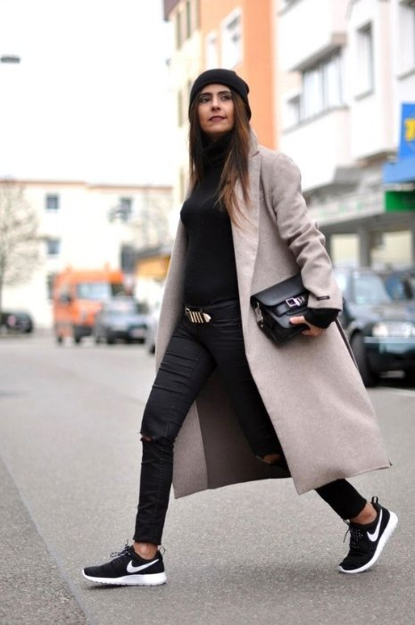woman wearing a black outfit with a grey overcoat and nike trainers