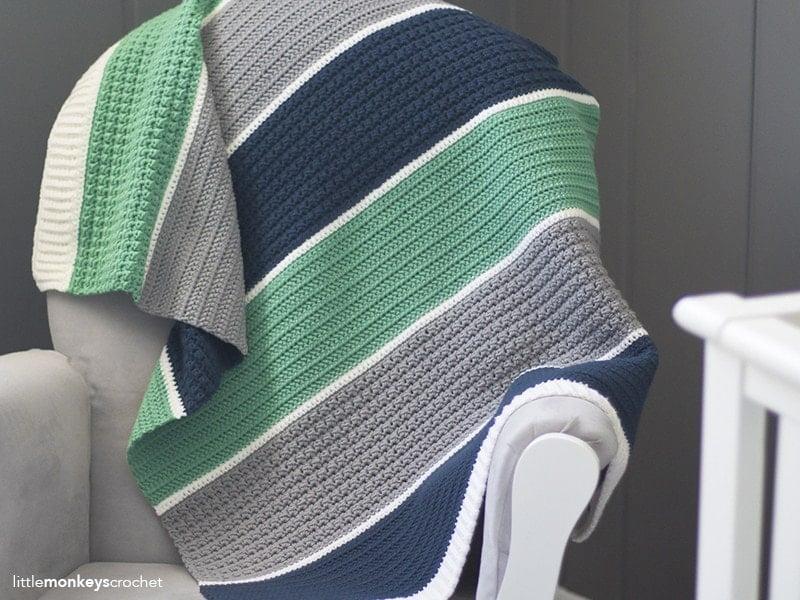 striped crochet blanket draped over an armchair