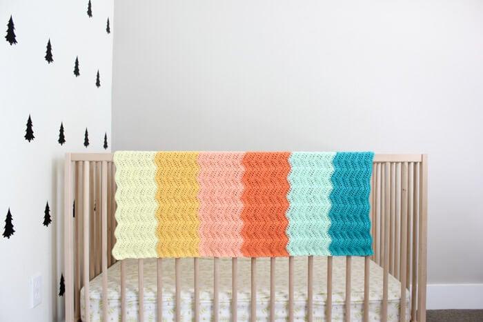 striped chevron baby blanket hanging on a crib