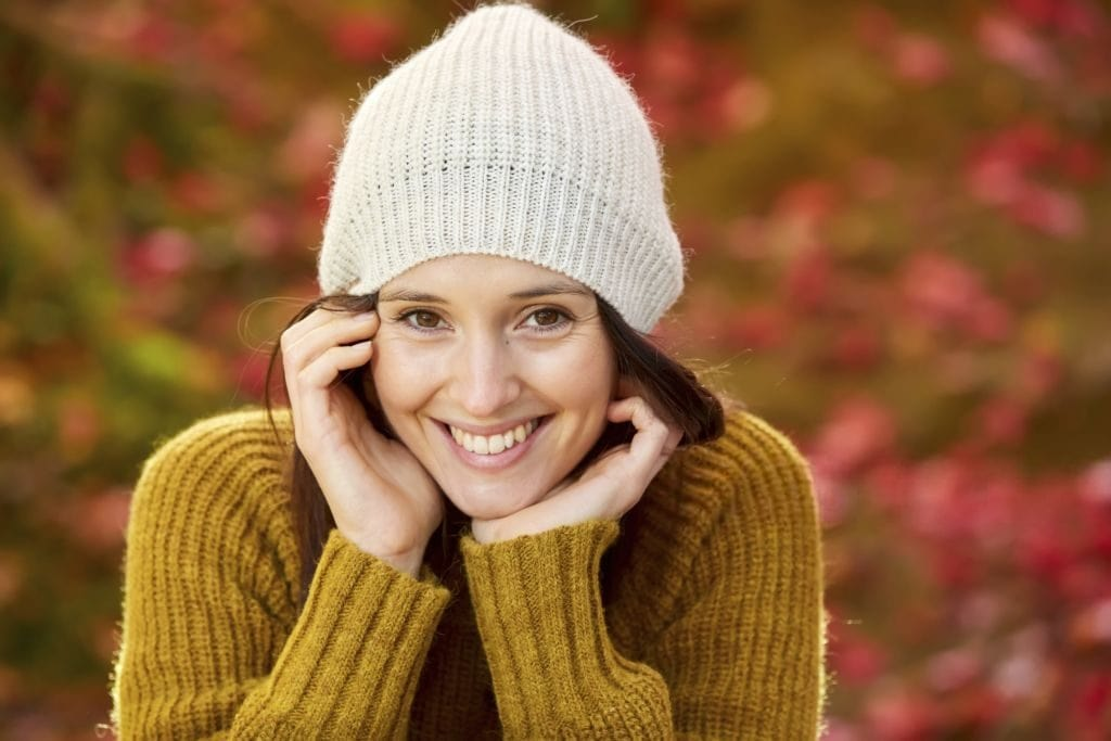 Woman wearing a white knitted hat and mustard coloured sweater