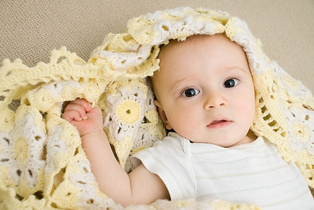 baby wrapped in a crochet blanket