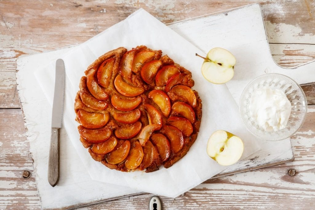 apple pie on a table with sliced apples and sugar