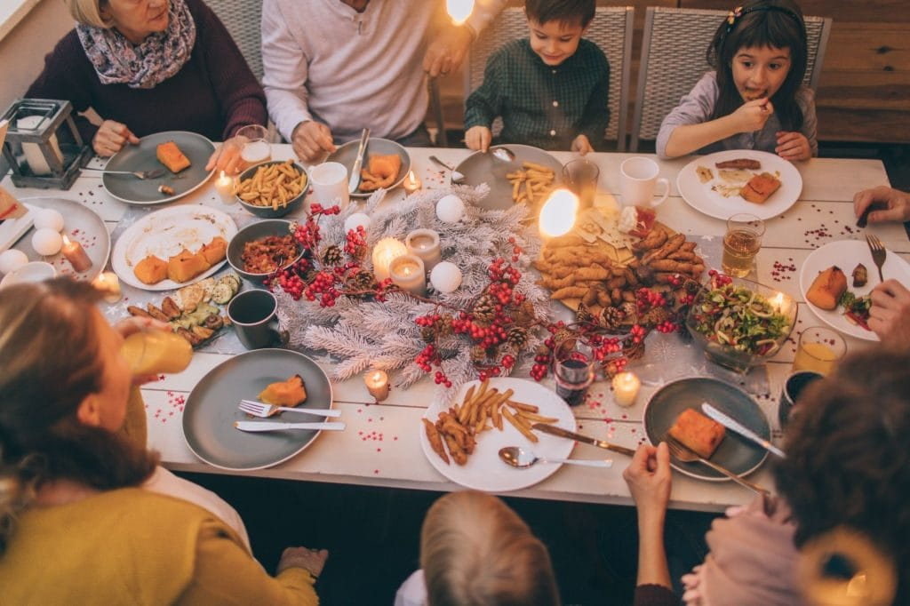 fall table decor with berries and a family eating