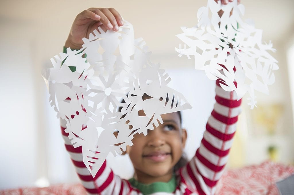 girl holding up a paper cut christmas snowflake