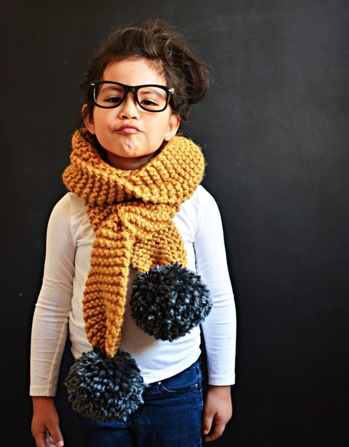 little girl wearing a knitted scarf
