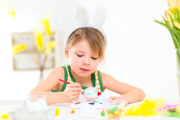 Child wearing bunny ears and painting an egg