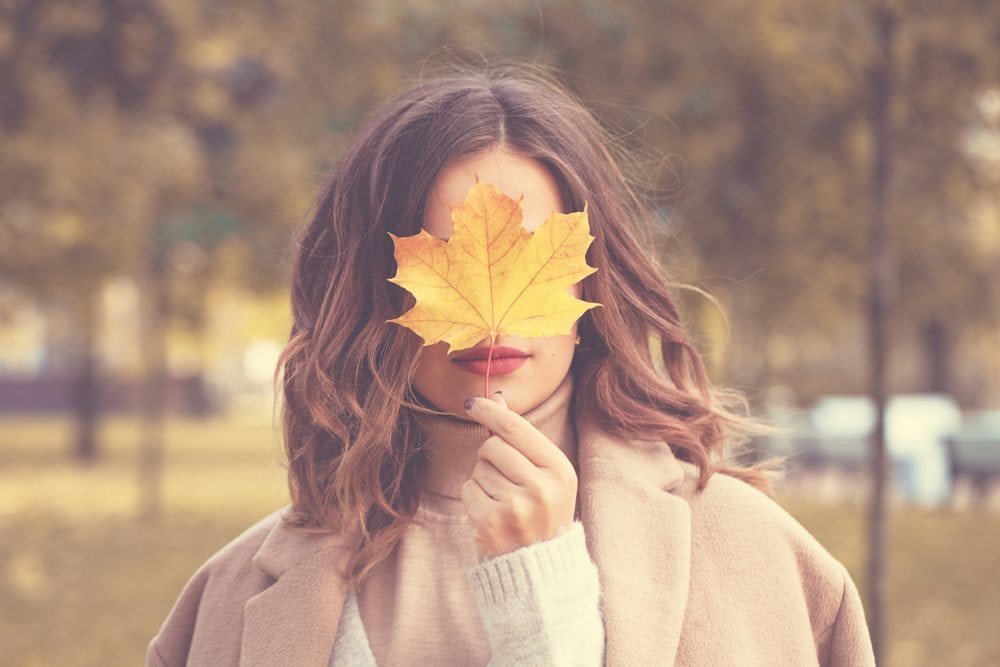 girl in fall with a maple leaf