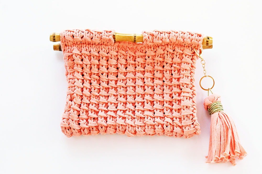 knitted clutch bag with bamboo handles and a tassel