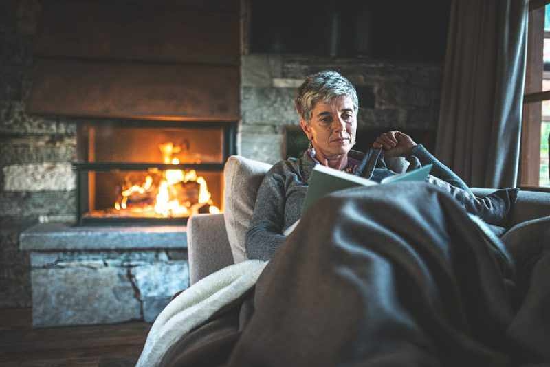 fall home decor ideas woman reading by a log fire