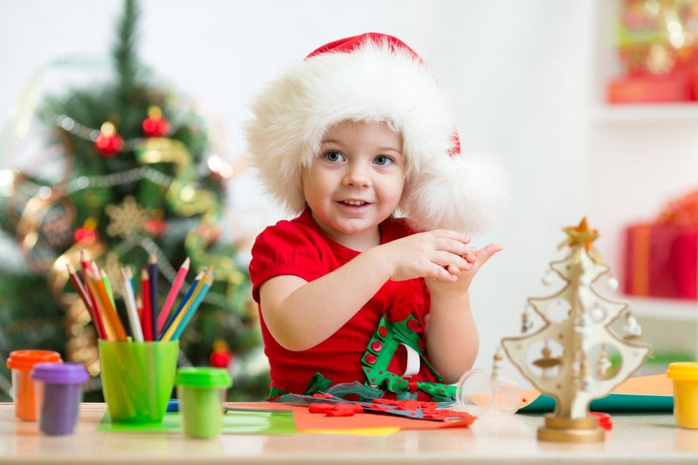 child wearing a Santa hat and crafting