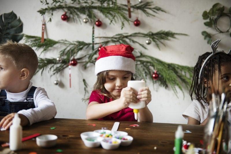 child wearing a Santa hat making Christmas crafts