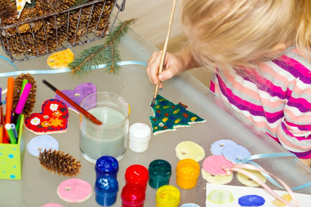 girl painting a Christmas tree decoration