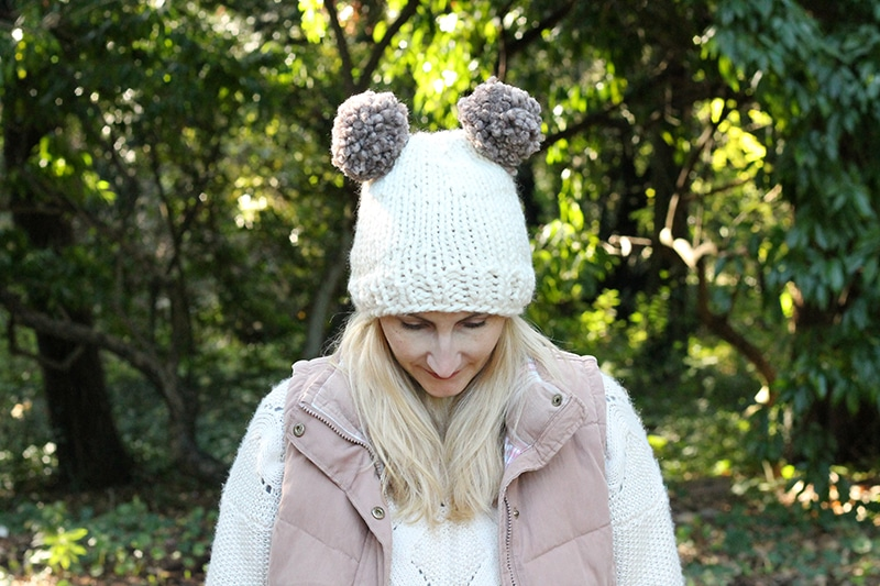 woman wearing double pom pom knitted hat