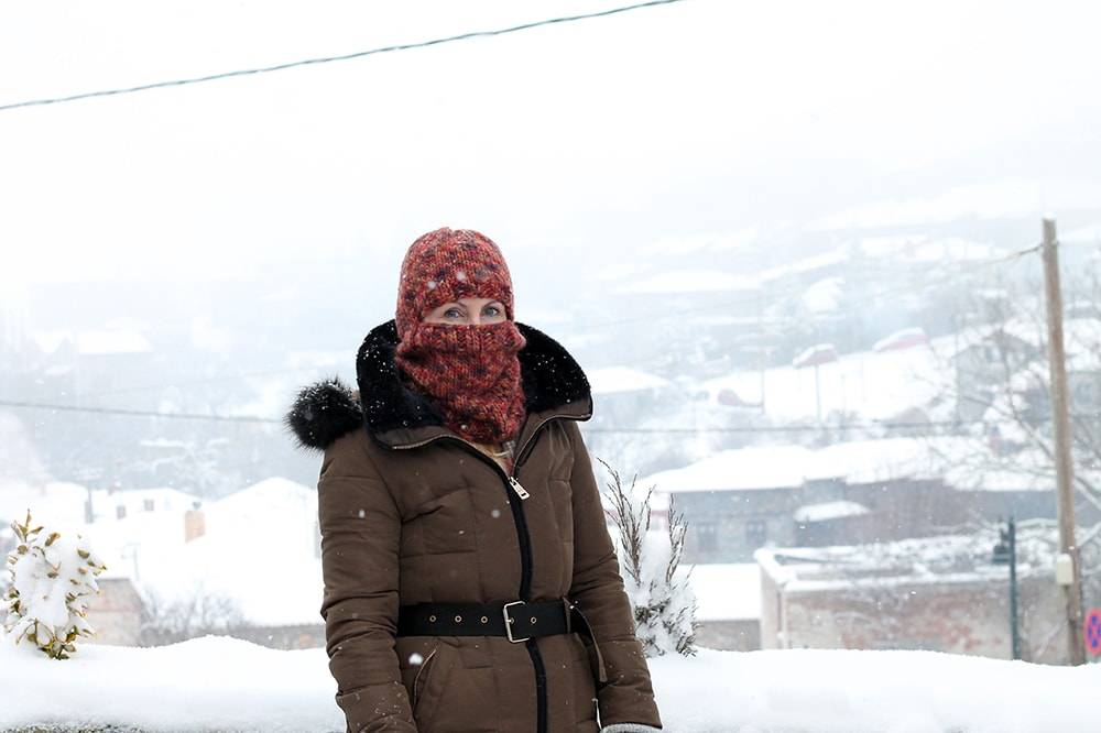 woman wearing a knitted ski mask in the snow