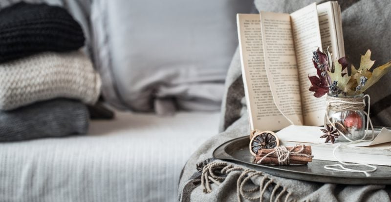 cozy fall living room with knitted blankets and a book