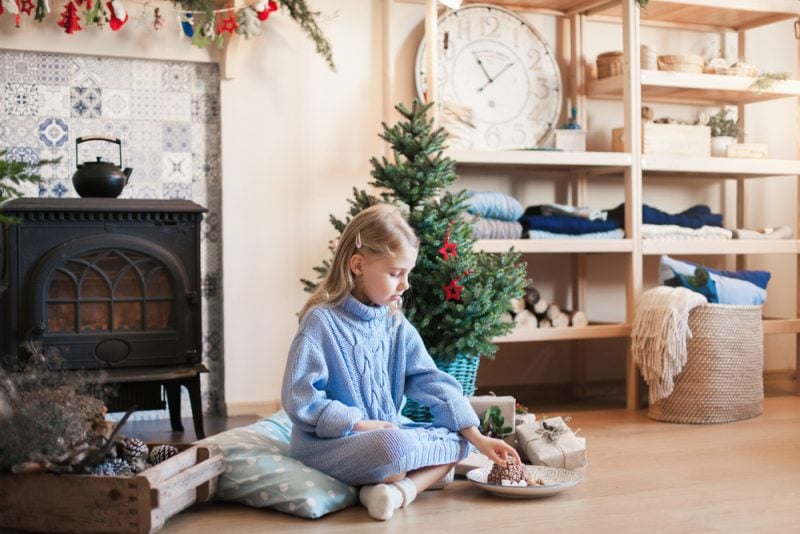 young girl sitting next to a Christmas tree