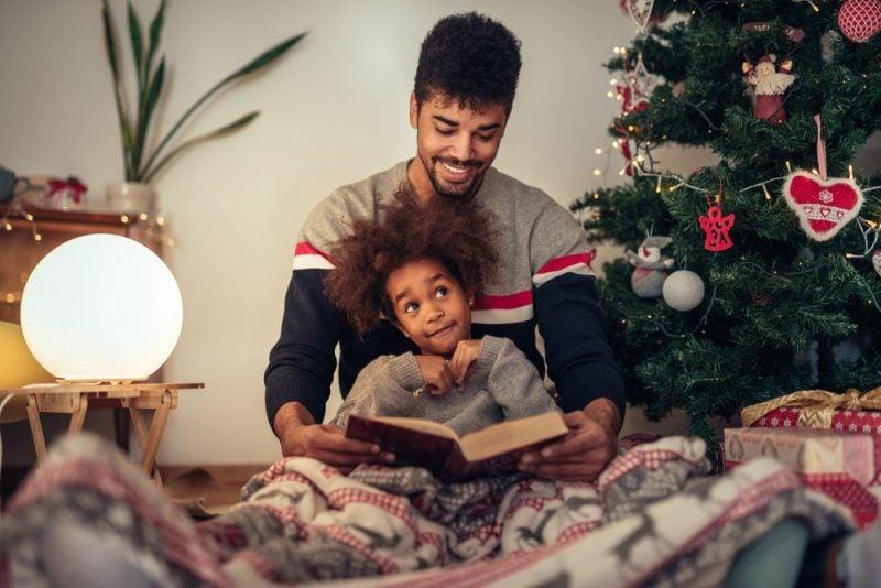 Family reading next to the Christmas tree