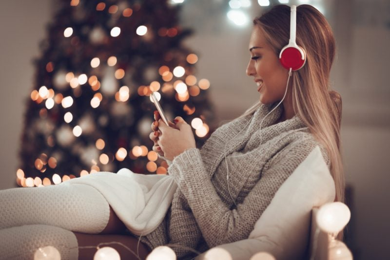 Woman listening to Christmas music next to a Christmas tree
