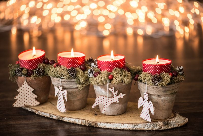 Christmas candles with red ribbon and wooden decorations