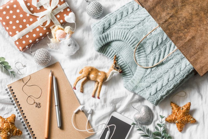 gift bag with cable sweater and other gifts