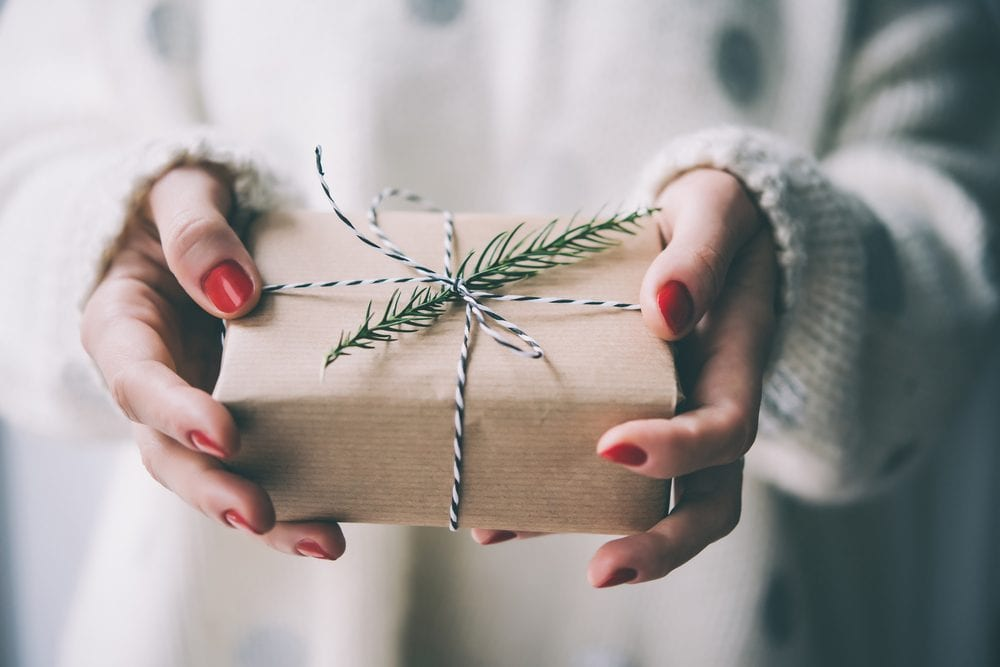 woman holding a wrapped gift in brown paper