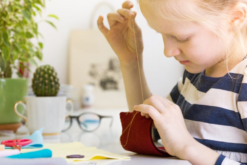 child sewing pieces of fabric together