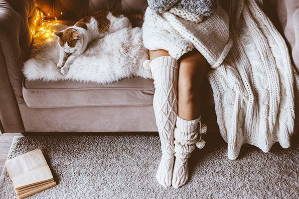 cozy living room with knitted blankets and girl wearing knee high socks
