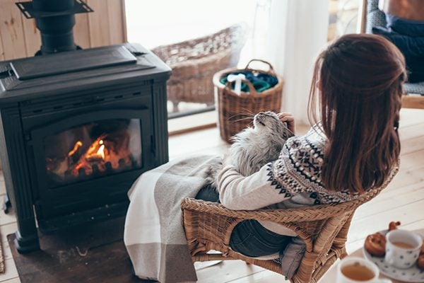 woman stroking pussy cat next to a log fire