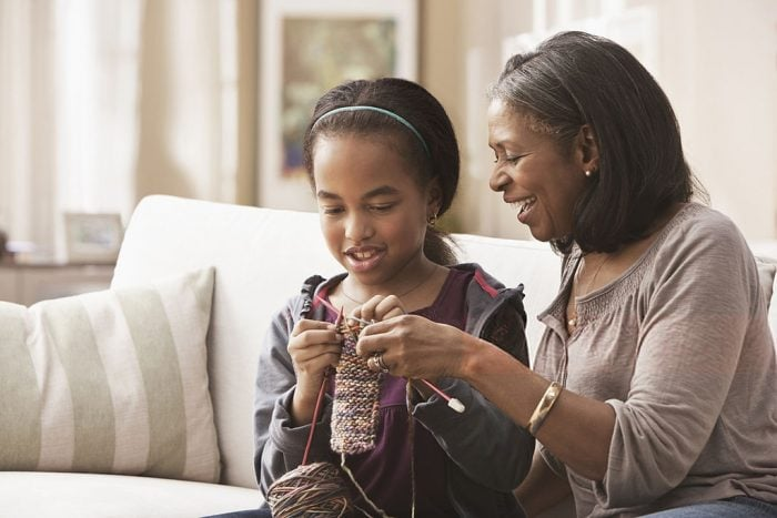 girl learning to knit from grandma