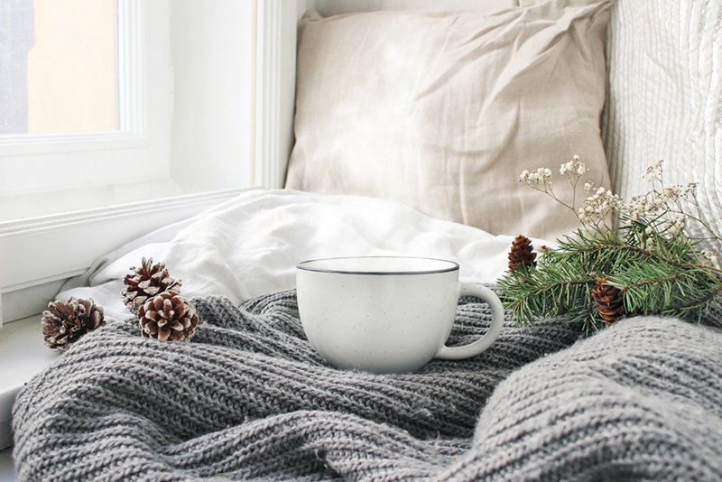 cosy bed with a knitted blanket and coffee cup