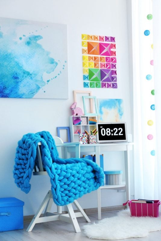 small craft room and chair with a chunky knit blanket