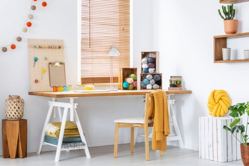 Craft room with a long desk and yarn storage