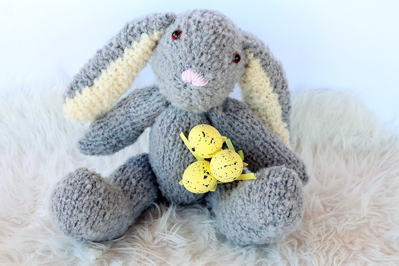 fluffy grey knitted easter bunny with yellow easter eggs