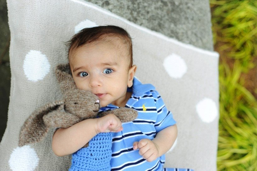 baby hugging a knitted bunny toy