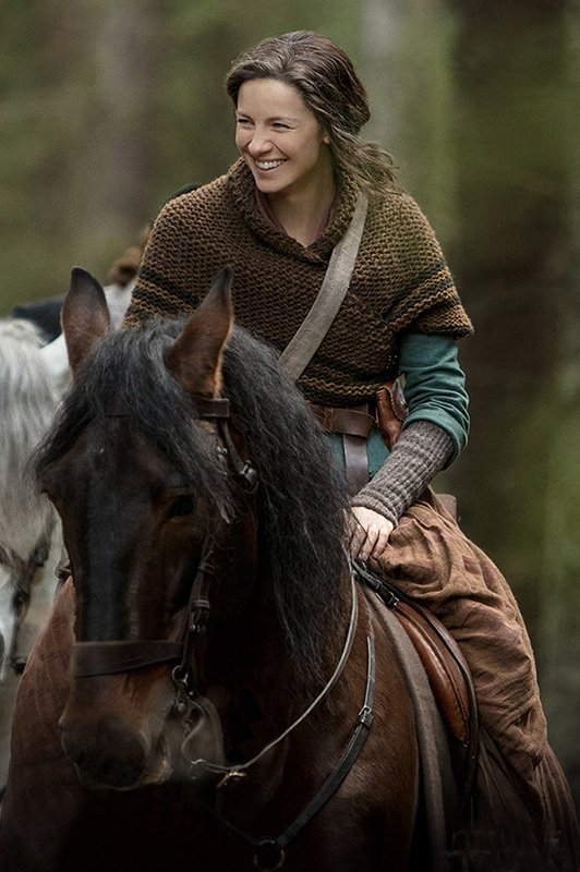 Claire from Outlander wearing a brown knitted shawl