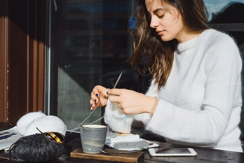 reader favourites girl knitting at a cafe in public