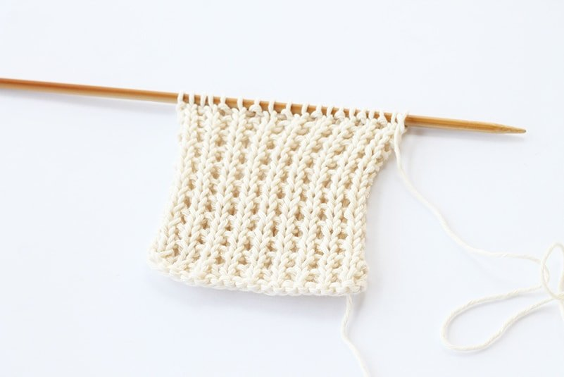 knitting stitches in white cotton on a knitting needle