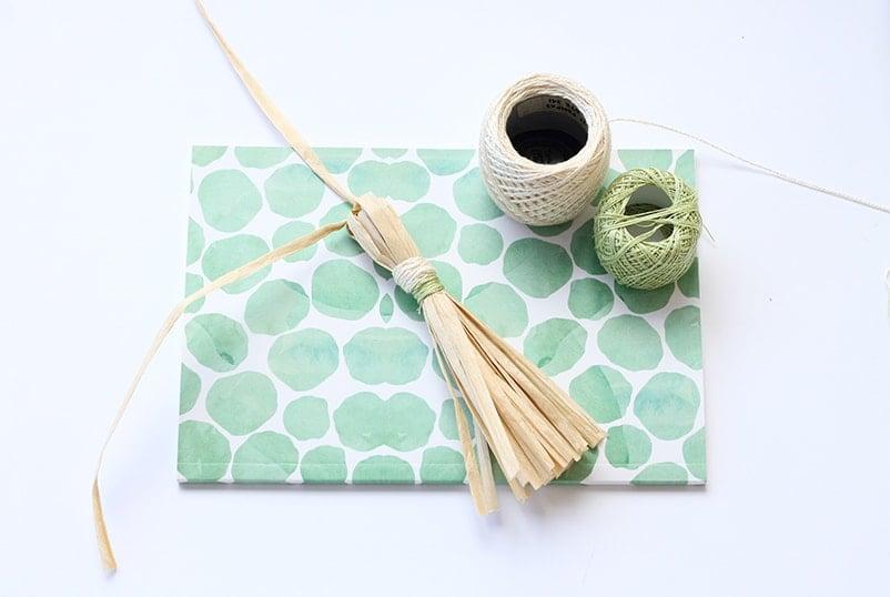 Raffia tassel lying on a notebook next to thread