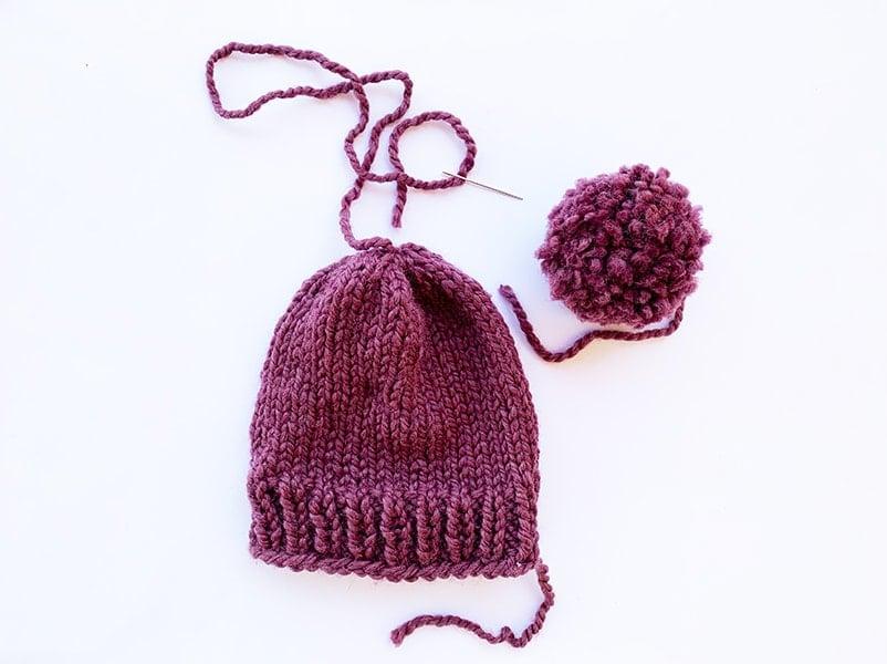 stitching a pom pom onto a hat