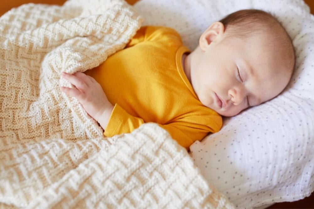 baby sleeping with a knitted blanket