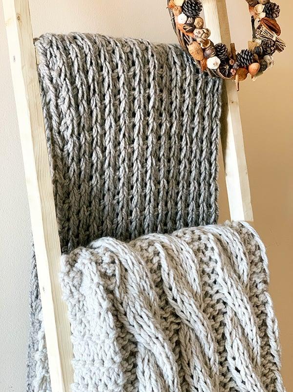 knitted blankets on a blnaket ladder