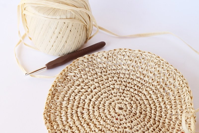 a circle made from raffia with a crochet hook