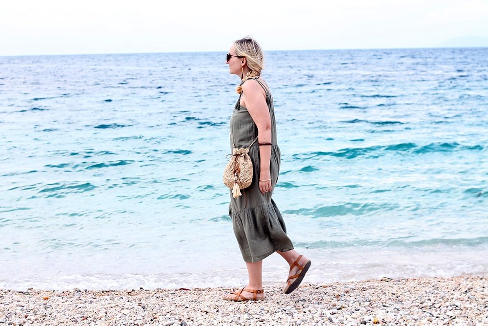 woman walking on the beach wearing a green dress and a crochet bag