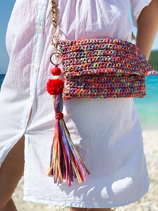 crochet summer bag made from raffia with a long tassel charm