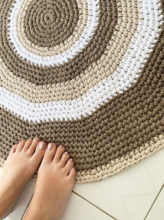 feet standing on a crochet bathrrom rug