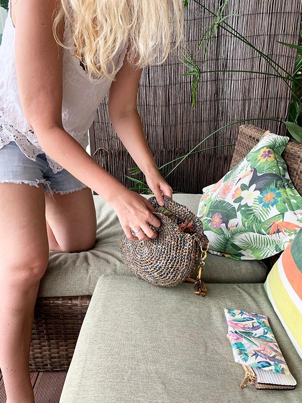 woman with a crochet raffia circle bag