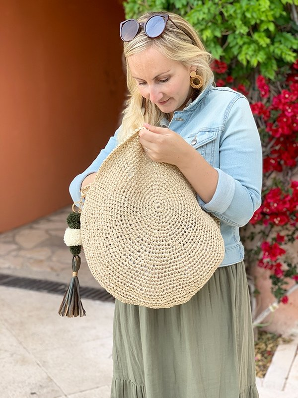 woman looking inside a raffia crochet bag with pom pom tassel
