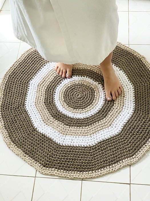 woman standing on a crochet circle rug in the bathroom