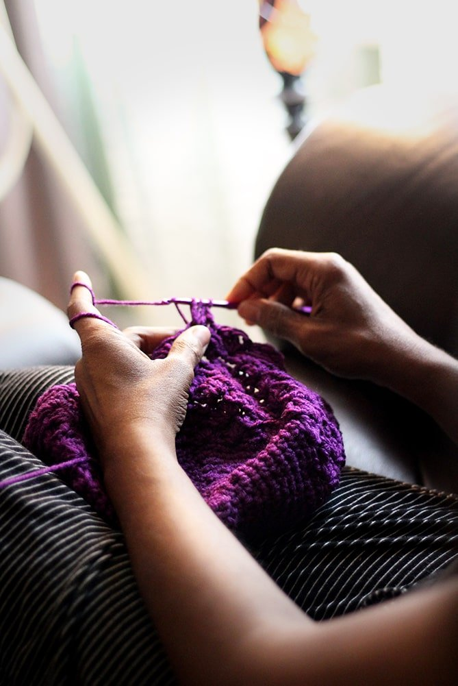 woman crocheting with yarn from her yarn stash