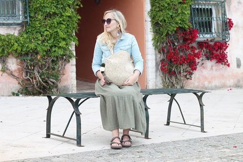 woman sitting on a bench holding a raffia circle bag